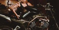 Woman mechanic repairing a motorcycle in a workshop