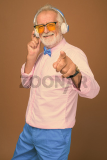Senior handsome man wearing stylish clothes against brown background