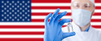Doctor holding a viol with vaccine against corona virus. Us flag on the background.