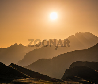Sun glow in evening hazy sky and mountain silhouettes view