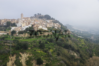 Foggy morning at the Hills of Polop de Marina with church and castell over green forest, Spain