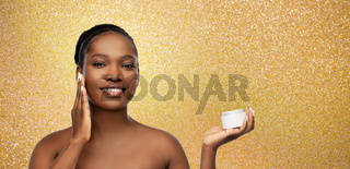 smiling african american woman with moisturizer