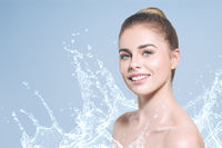 Young beautiful woman portrait with water splashes. Body and skin care wash in bathroom or showering