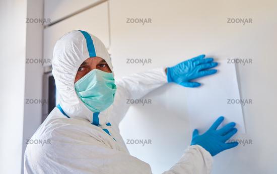 Personal in Klinik mit Schutzkleidung befestigt Aushang