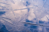 Beautiful pattern in the ice with reflecting clouds