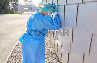 Arzt in Schutzkleidung bei Coronavirus Pandemie ist überlastet vor Klinik