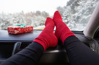 The legs of a girl in red socks sits in the car in the winter, against the background of a winter forest. Travel, trip and winter concept.