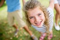 Lachendes Mädchen spielt mit Eltern im Garten