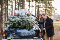 Joyful couple near the vintage car with presents on roof