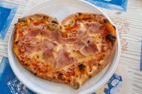 Heart shape prosciutto pizza on white plastic plate