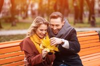 Young embracing happy romantic couple sitting gently hugged on a bench in park wearing coats and scarfs. A romantic couple sitting on a bench hugging in the park. Love story