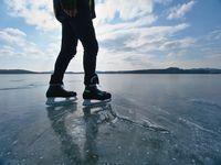 Legs of unrecognizable sportsman in ice skates. Man stay on frozen lake
