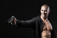 evil smiling man shooting gun isolated on black