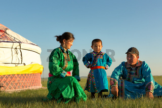 Nomadic Mongolian family with their traditional colorful dresses near their yurt