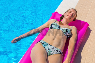 Dutch woman sunbathes on air mattress at pool
