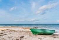 small green boat on empty sand beach against sea
