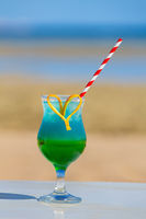 Colorful cocktail drink in glass at beach