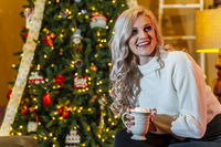 A lovely young Blonde model enjoys the holiday season at home with a Christmas tree and presents