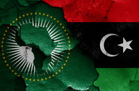flags of African Union and Libya painted on cracked wall