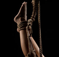 Nude girl tied up with rope hanging upside down
