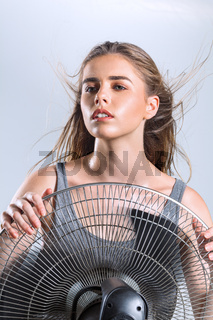 Young woman enjoying cool air wind from electric fan at hot summer season heat wave