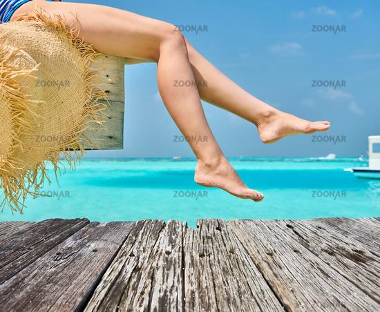 Woman sitting at beach jetty