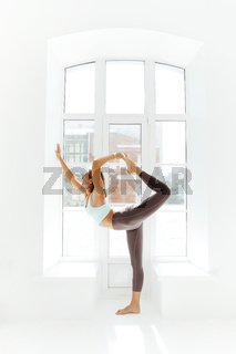 Flexible woman doing yoga at home