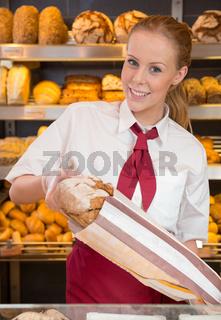 Shopkeeper in baker's shop selling bread to customer
