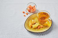 Delicious black tea in glass cup and candied fruits on yellow saucer