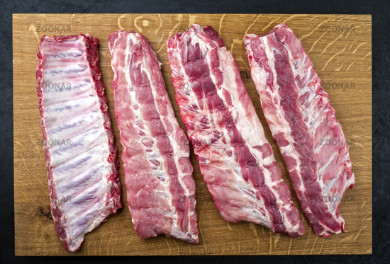 Raw pork spare loin ribs St Louis cut offered as top view on a wooden board