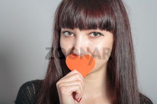 Woman is holding paper heart in front of her mouth