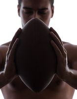 Ripped young man with american football isolated on white