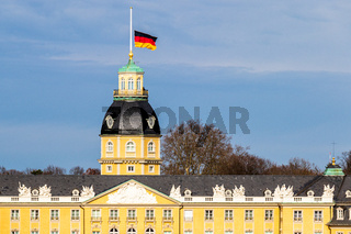 Roof of Castle Karlsruhe, with German Flag at Halfmast, auf Halbmast, on the tower roof in winter. In Baden-Württemberg, Germany