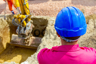 Boss oversees, controlling excavator until is digging on building site
