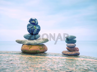 Rounded pebbles stack in peaceful evening with smooth ocean