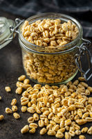 Puffed wheat covered with honey in jar. Cereal breakfast.