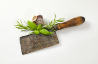 Vintage meat cleaver and fresh herbs