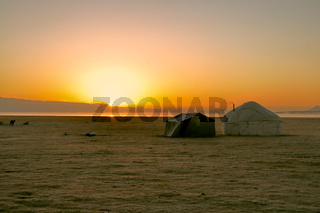 Sun rising over traditional yurt of nomadic tribe on green grasslands in Kyrgyzstan