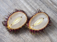 Two halves of a rambutan on a wooden background.