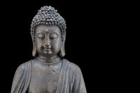 Upper body of a buddha statue with patina isolated on black background