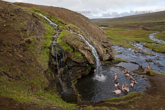 People bathing at the natural warm waterfall with pool, Laugarvallardalur, Iceland, Europe