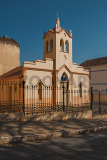 Facade of small church and belfry behind iron fence in a sunny day at Sao Manuel