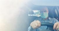 Autofahrer mit Mundschutz beim Auto fahren