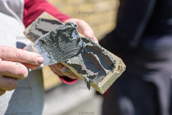 Man applies glue with spatula on decorative facing brick, view close up. Theme of construction