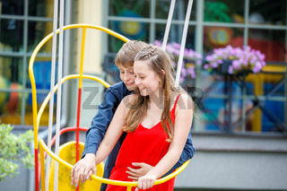 young guy with a girl on a swing in the park