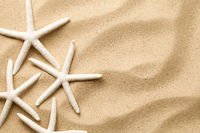 Starfishes On Sand Background