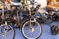 collection of little models of old steel bicycles displayed in an antiques market