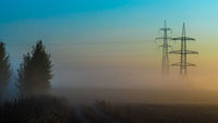 A foggy morning in an autumn field with a power line and a country road