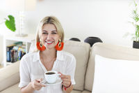Stylish woman drinking coffee at home