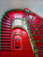 Historical old staircase lined with red linoleum
